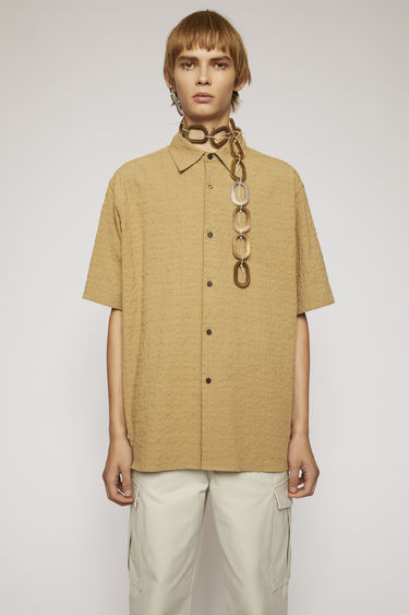 Acne Studios mushroom beige short-sleeved shirt is made from lightweight seersucker and finished with a point collar and button-down front.