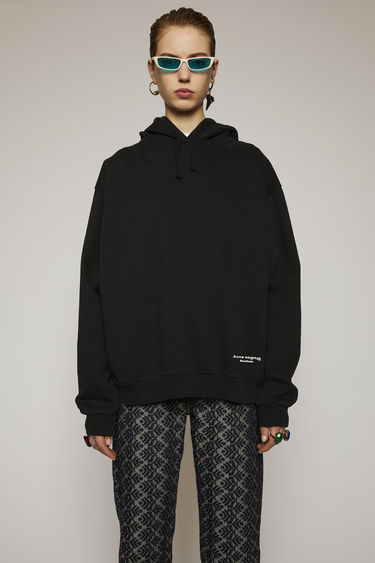 Acne Studios black hooded sweatshirt is cut to an oversized fit from cotton jersey and features contrasting tape that's purposefully applied with irregular folds at the side seams.