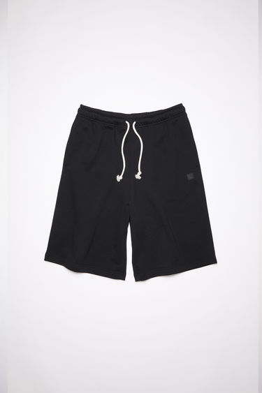 Acne Studios black relaxed fit sweat shorts are made of unbrushed cotton fleece and feature tonal embroidered face patches.