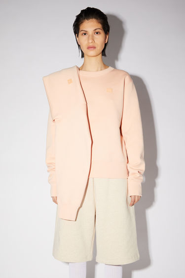 Acne Studios powder pink regular fit crew neck sweatshirt features ribbed details and a face patch on the front.
