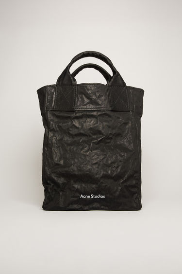 Acne Studios black tote bag is made from malleable cotton and nylon blend to create a crumpled, boxy silhouette. It features a top handle, adjustable shoulder strap and a logo print across the front.