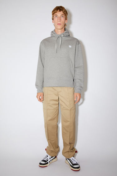 Acne Studios Ferris Face light grey melange hooded sweatshirt is made from midweight brushed jersey with a kangaroo pocket and accented with a tonal face-embroidered patch on the chest.
