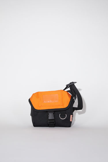 Acne Studios black/orange durable small messenger bag has an adjustable hard plastic buckle closure and Acne Studios logo tab.