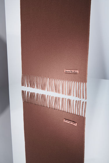 Acne Studios caramel brown narrow fringed scarf is made of pure wool, featuring a label in one corner.