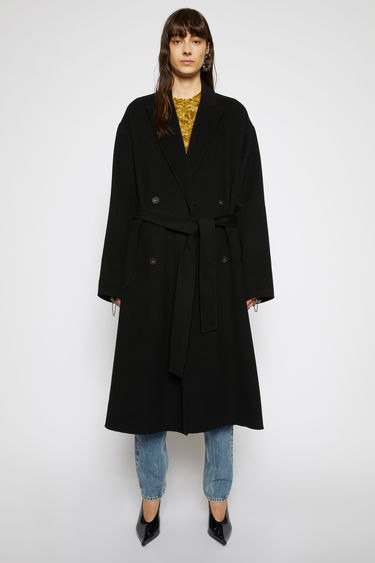Acne Studios black belted coat is crafted from double-faced wool to a relaxed silhouette and features peak lapels, dropped shoulders and a double-breasted front.
