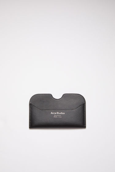Acne Studios Elmas S black cardholder is crafted from soft grained leather with three card slots and accented with a cut-out at the midpoint of the central slot.