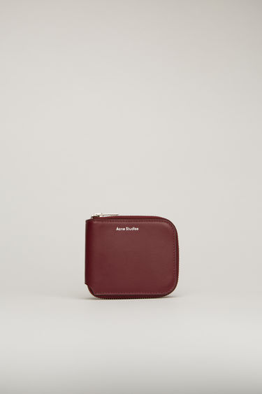 Acne Studios burgundy wallet is crafted from soft grained leather to a bi-fold design and has a wraparound zip that opens to reveal two card slots and a note sleeve.