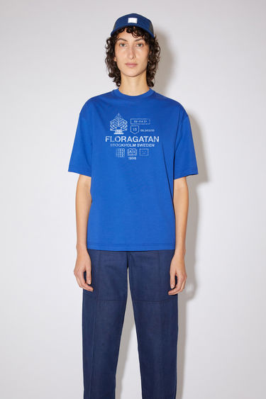 Acne Studios electric blue relaxed fit t-shirt is made of organic cotton with a ribbed crew neck and distressed print.