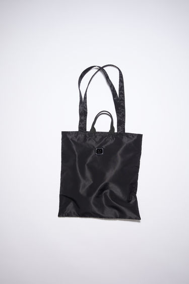 Acne Studios black tote bag is made from recycled polyester, featuring both carrying handles and shoulder straps. It has a mesh-lined interior pocket and tonal metal logo plaque.