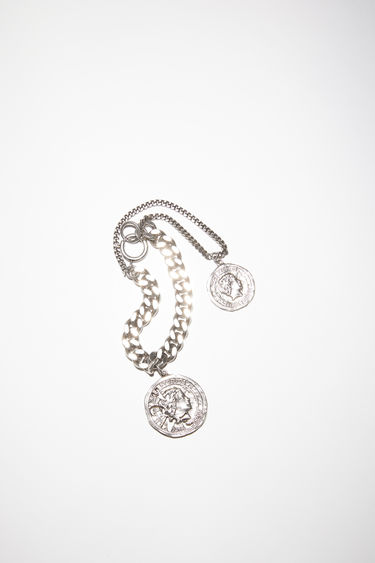 Acne Studios antique silver charm bracelet features two branded coins on fine and thick chains.