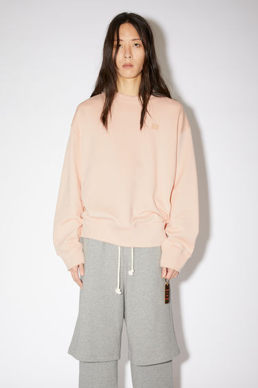 Acne Studios powder pink oversized crew neck sweatshirt is made of organic cotton with a face patch and ribbed details.