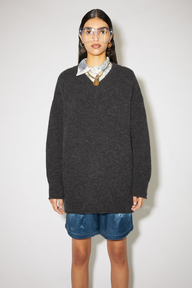 Acne Studios washed black sweater is crafted from soft alpaca and wool-blend to a relaxed silhouette with a deep v-neckline and finished with rolled edges around the ribbed cuffs and hem.