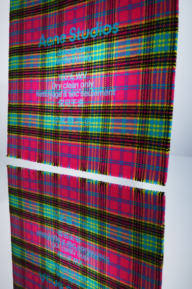 Acne Studios fuchsia/turquoise tartan check scarf is made of wool with a large, printed care label.