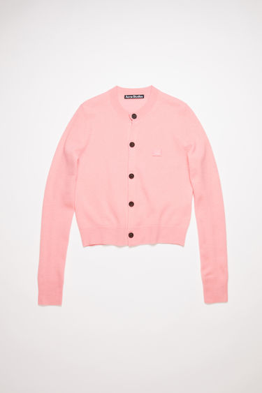 Acne Studios blush pink crew neck cardigan sweater is made from wool with a face logo patch and ribbed details.