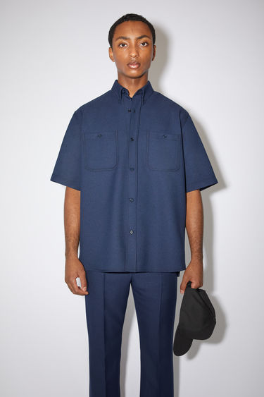 Acne Studios spruce blue short sleeve shirt is made of polyester twill with a boxy fit.