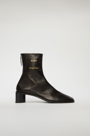 Acne Studios black/black boots are crafted to a slim silhouette from supple leather and set on a stacked block heel. They are accented with a metal zip and a gold stamped logo on the ankle.