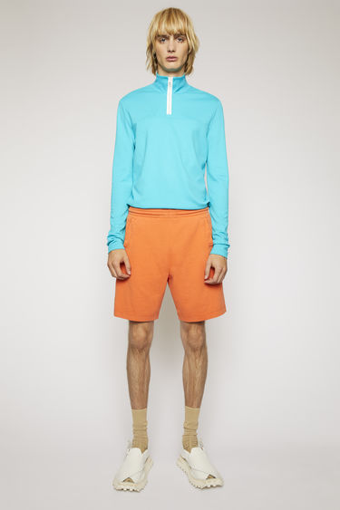 Acne Studios mandarin orange shorts are made from brushed cotton jersey with a washed out finish and features an elasticated drawstring waist and a reversed logo print.
