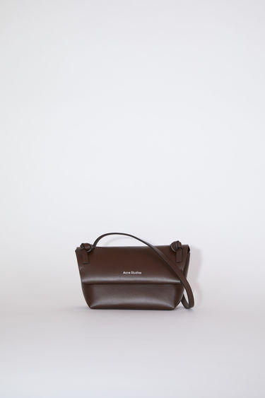 Acne Studios dark brown flap purse features twisted knots inspired by traditional Japanese obi sashes.