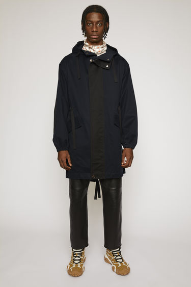 Acne Studios navy/black parka is cut from technical cotton twill with a tonal placket and features a drawstring hood, waist and hem to adjust the fit.