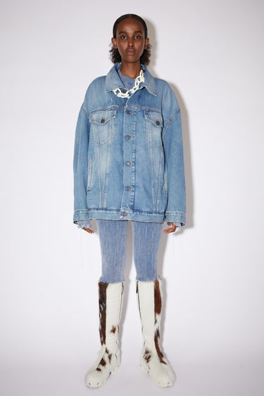 Acne Studios rodeo blue jacket is crafted from rigid denim that's treated with a stone wash for a worn-in appeal. It's crafted to an oversized silhouette with dropped shoulders and an extended hem, then fitted with an array of slip and patch pockets.