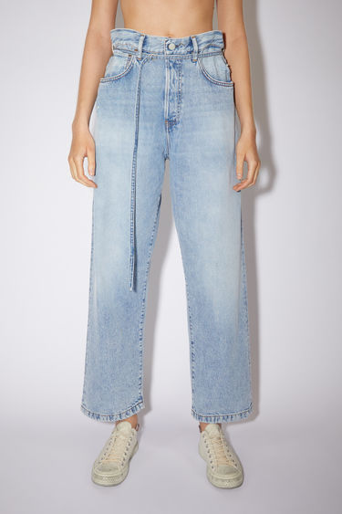 Acne Studios 1991 Toj light blue jeans are crafted from rigid denim with wide, straight legs that's been lightly stonewashed. They can be worn on the natural waistline or pulled to a high rise with a matching belt. The female model is wearing two sizes larger than her actual size to achieve a looser fit.