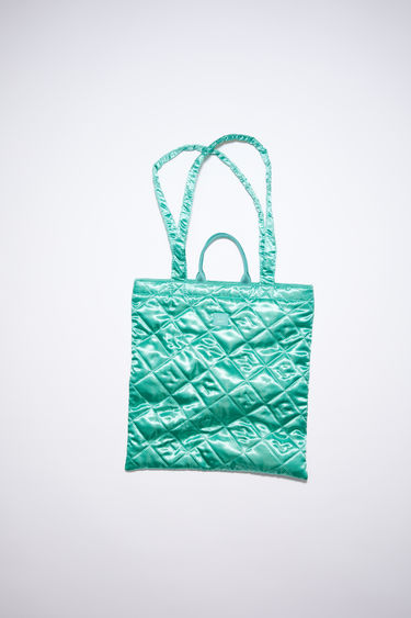 Acne Studios jade green shiny tote bag features face quilting with carrying handles and shoulder straps.