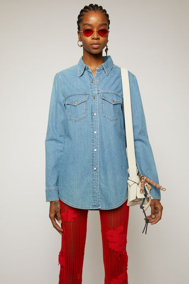Acne Studios light blue denim shirt is crafted to a slim silhouette with front and back yokes and accented with antiqued metal press-studs and patch pockets.