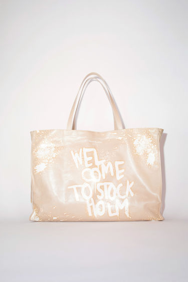 Acne Studios ecru beige oilcloth tote bag features a Welcome to Stockholm graffiti print.