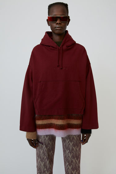 Acne Studios Joghy chocolate brown is an oversized hooded sweatshirt with embossed logo on the chest.