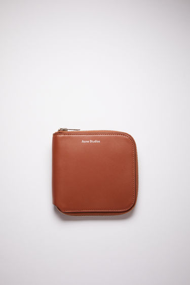 Acne Studios almond brown leather wallet is crafted from grained leather to a bifold design and has a wraparound zip that opens to reveal a coin pocket, note sleeve and card slots.