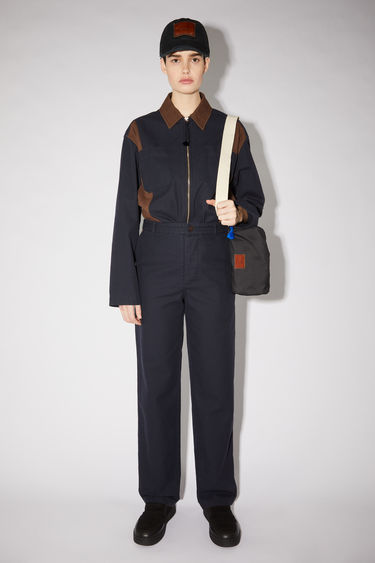 Acne Studios navy/dark brown workwear trousers are made of organic stonewashed cotton with a straight leg and contrasting pocket panels and a face patch.