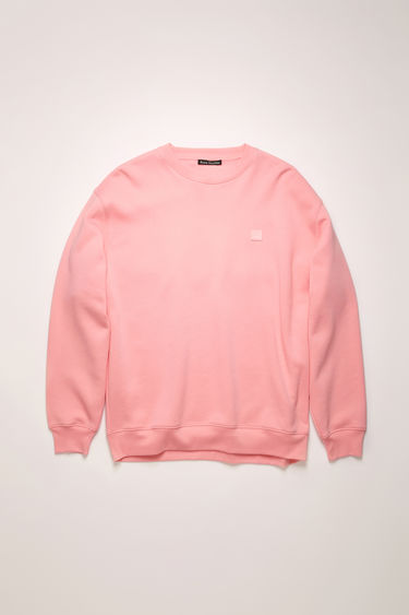 Acne Studios blush pink sweatshirt is crafted from midweight loopback fleece to a loose silhouette and finished with a face-embroidered patch on the chest.