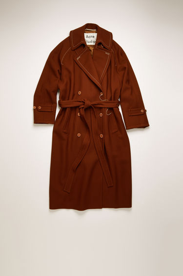 Acne Studios rust brown trench coat is crafted from wool-twill with raglan sleeves and an oversized back storm flap and accented with thick topstitching and whipstitched buttons.