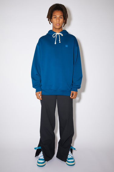 Acne Studios teal blue oversized hooded sweatshirt is made of organic cotton with a face logo patch and ribbed details.