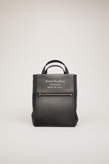 Acne Studios Baker Out S black/black is a small tote bag with an embossed logo pocket placed outside of the bag.