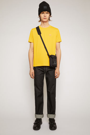 Acne Studios honey yellow t-shirt is cut from a lightweight cotton jersey to a slim-fitting silhouette with a round neckline and accented with a tonal face-embroidered patch on the chest.