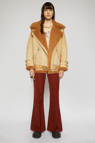 Acne Studios Velocite Suede beige shearling jacket is lined with soft lamb shearling and accented with buckled leather straps at the neck, cuffs and hem.