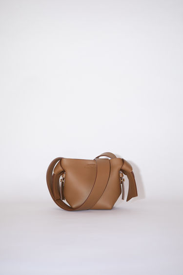 Acne Studios camel brown small bag features twisted knots inspired by traditional Japanese obi sashes. It has a debossed logo, magnetic closure, and detachable strap with handles for wear as either a shoulder or handbag.
