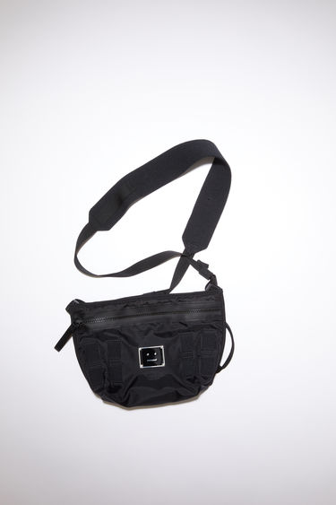 Acne Studios black crossbody bag is made from technical ripstop and features a silver-tone metal logo plaque with a face motif in black. It has a front zipper pocket, mesh pocket, and an adjustable buckle strap.