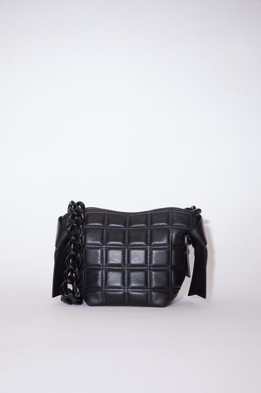 Acne Studios Musubi Mini black bag features twisted knots inspired by traditional Japanese obi sashes. It's crafted from quilted lamb leather with a top handle and detachable chain strap and has a press-stud fastening which opens to reveal a leather-lined interior with a zipped divider.