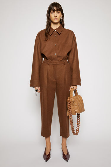Acne Studios cognac brown trousers cut with a high waist and cropped, tapered legs, and are pleated along the front for subtle volume.