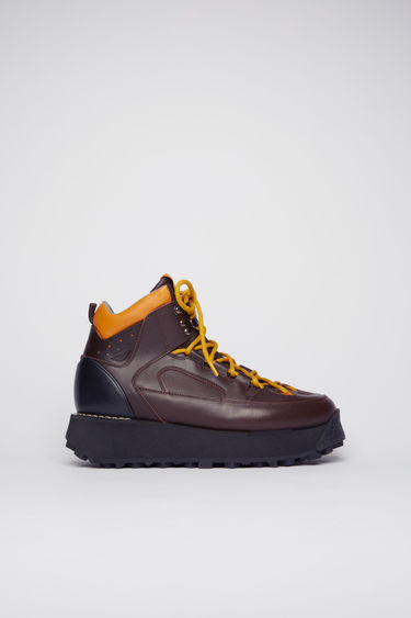 Acne Studios brown boots take cues from functional elements of hiking gears. They're crafted from soft grained leather accented with a padded ankle cuff and rope-style laces, then set on a lug sole.