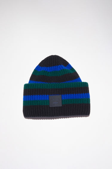 Acne Studios black/blue striped beanie hat is made from rib knit wool with a face logo patch.
