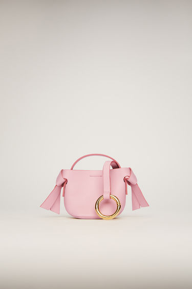 Acne Studios rose pink Musubi keychain is crafted from soft grained leather with twisted knots and secured with a logo-engraved metal clasp that allows it to be attached to your key ring or belt loop.