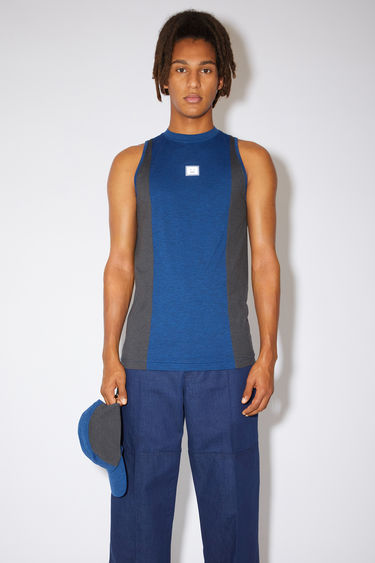 Acne Studios teal blue colour block tank top is made of lightweight technical jersey with a reflective face logo at the chest.