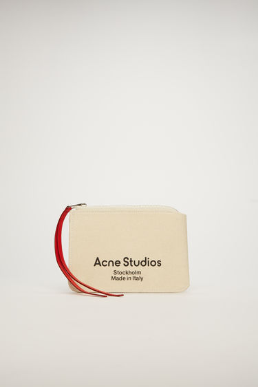 Acne Studios beige zip wallet is crafted from cotton-canvas with rounded edges and features a red leather zip puller and a logo embossed in black across the front.