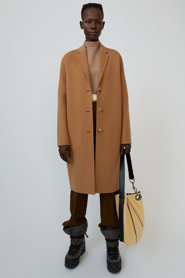 Acne Studios Avalon Double camel brown is a tailored wool coat finished with handstitched double construction.This style is designed for an oversized fit. We recommend taking a size smaller.
