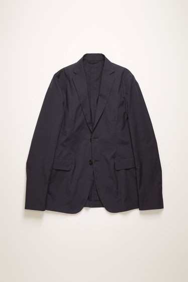 Acne Studios dark blue suit jacket is crafted from lightweight cotton poplin that's cut to a slim-fit silhouette. It's partially lined and has unstructured shoulders and notch lapels.