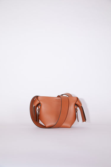 Acne Studios almond brown small bag features twisted knots inspired by traditional Japanese obi sashes. It has a debossed logo, magnetic closure, and detachable strap with handles for wear as either a shoulder or handbag.
