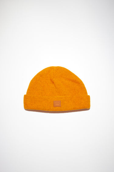 Acne Studios carrot orange beanie hat is made from rib knit wool with a face logo patch.